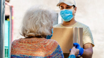 masked person handing a box to a senior lady